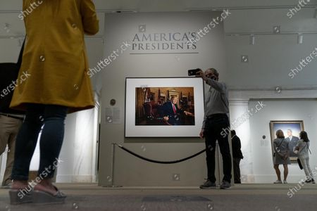 Man who identified himself only as Jeff, takes a selfie with a photograph of former President Donald Trump by Pari Dukovic as it hangs in the America's Presidents exhibition at the Smithsonian's National Portrait Gallery in Washington