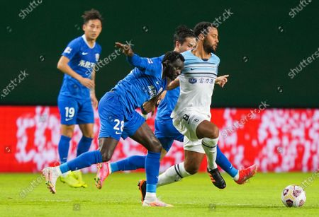 (210514) - GUANGZHOU, May 14, 2021 (Xinhua) - Mousa Dembele (1StR) of Guangzhou City competes against Senghor (2nd L) of Cangzhou Mighty Lions during the 5th round match between Guangzhou City and Cangzhou Mighty Lions at the 2021 season Chinese Football Association Super League (CSL) Guangzhou Division in Guangzhou, South China's Guangdong Province, May 14, 2021.
