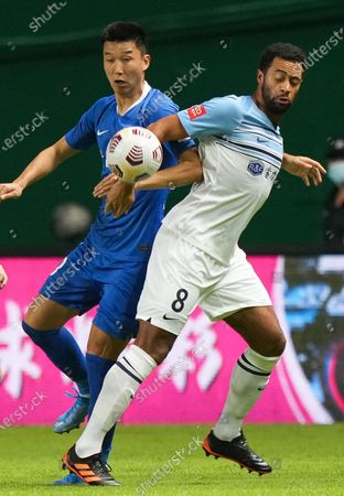 Stock Photo of (210514) - GUANGZHOU, May 14, 2021 (Xinhua) - Mousa Dembele (R) of Guangzhou City competes during the 5th round match between Guangzhou City and Cangzhou Mighty Lions at the 2021 season Chinese Football Association Super League (CSL) Guangzhou Division in Guangzhou, South China's Guangdong Province, May 14, 2021.