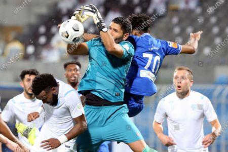 Al-Hilal's player Mohammed Jahfali (up-back) in action against Al-Batin's goalkeeper Martin Campana (up-front) during the Saudi Professional League soccer match between Al-Hilal and Al-Batin at Prince Faisal Bin Fahd Stadium, Riyadh, Saudi Arabia, 14 May 2021.