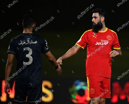 Al-Ahli's player Mohammed Al-Fatil (L) shakes hands with Al-Qadisiyah's Rhys Williams (R) during the Saudi Professional League soccer match between Al-Ahli and Al-Qadisiyah at Sport Hall Stadium in King Abdullah Sport City, Jeddah, Saudi Arabia, 14 May 2021.