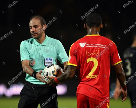 Al-Qadisiyah's player Carolus Andria (R) gives the ball to Saudi referee Turki Al Khudair (L) during the Saudi Professional League soccer match between Al-Ahli and Al-Qadisiyah at Sport Hall Stadium in King Abdullah Sport City, Jeddah, Saudi Arabia, 14 May 2021.