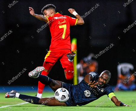 Al-Ahli's player Motaz Hawsawi (down) in action against Al-Qadisiyah's Hassan Al-Amri (up) during the Saudi Professional League soccer match between Al-Ahli and Al-Qadisiyah at Sport Hall Stadium in King Abdullah Sport City, Jeddah, Saudi Arabia, 14 May 2021.