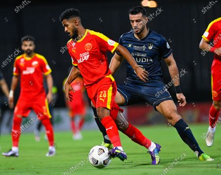 Al-Ahli's player Omar Al-Somah (R) in action against Al-Qadisiyah's Ibrahim Al-Sheail (L) during the Saudi Professional League soccer match between Al-Ahli and Al-Qadisiyah at Sport Hall Stadium in King Abdullah Sport City, Jeddah, Saudi Arabia, 14 May 2021.