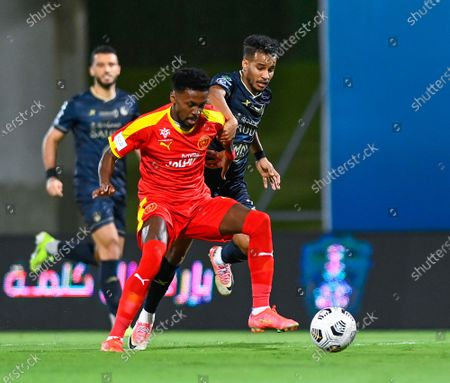 Al-Ahli's player Abdulrahman Ghareeb (R) in action against Al-Qadisiyah's Hamad Al Yami (L) during the Saudi Professional League soccer match between Al-Ahli and Al-Qadisiyah at Sport Hall Stadium in King Abdullah Sport City, Jeddah, Saudi Arabia, 14 May 2021.