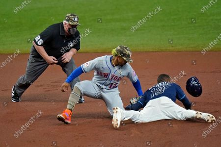 New York Mets shortstop Francisco Lindor (12) tags out Tampa Bay Rays' Manuel Margot (13) attempting to steal second base during the first inning of a baseball game, in St. Petersburg, Fla. Making the call is umpire Bill Miller