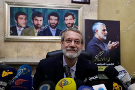 Former Iranian parliament speaker Ali Larijani speaks to journalists at the Iranian Embassy in Beirut, Lebanon. Larijani registered to potentially run in the Islamic Republic's upcoming presidential election, becoming the first high-profile candidate to potentially back the policies of the outgoing administration that reached Tehran's tattered nuclear deal with world powers. Larijani spoke in front of a painting of four missing Iranian diplomats who disappeared during the 1982 Israeli invasion of Lebanon, left, and a picture of the late Iranian Quds Force top commander Qassem Soleimani, right