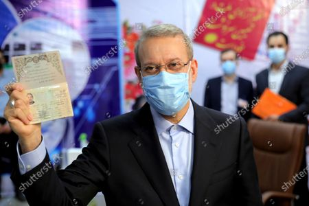 Former Iranian parliament speaker Ali Larijani shows his identification document while registering his name as a candidate for the June 18 presidential elections at elections headquarters of the Interior Ministry in Tehran, Iran
