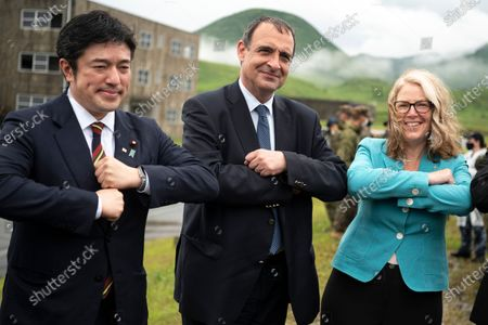 From left, Japan's Deputy Defense Minister Yasuhide Nakayama, French Ambassador to Japan Philippe Setton, Australian Ambassador to Japan Jan Adams pose for pictures during a joint military drill between Japan Self-Defense Force, French army and U.S. Marines, at the Kirishima exercise area in Ebino, Miyazaki prefecture, southern Japan