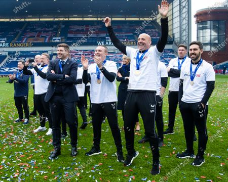 Stock Photo of Rangers Manager Steven Gerrard and Assistant Manager Gary McAllister watch their players lift the Scottish Premiership trophy at Ibrox Stadium.