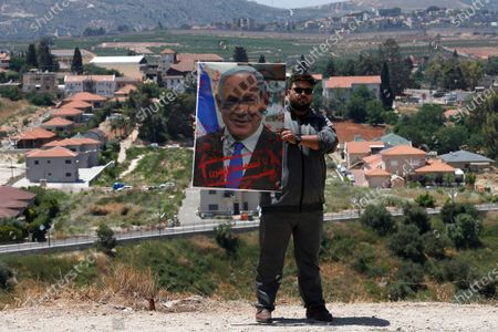 """Lebanese man holds a portrait of the Israeli Prime Minister Benjamin Netanyahu with Arabic words """"No to the deal of the century,"""" as he stands in front of the Israeli settlement of Metula, background, on the Lebanese side of the Lebanese-Israeli border in the southern village of Kfar Kila, Lebanon, . On Israel's northern border with Lebanon, Israeli troops opened fire on Friday when a group of Lebanese and Palestinian protesters on the other side cut through the border fence and briefly crossed"""