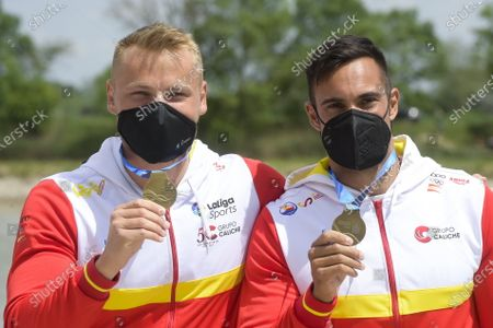 Marcus Walz (L) and Rodrigo Germade (R) of Spain pose with their gold medals on the podium after winning the men's K2 500m final of the ICF Canoe Sprint World Cup in Szeged, Hungary, 15 May 2021.