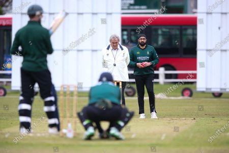 Ex-England International cricketer Monty Panesar playing for Twickenham Cricket Club while he studies for an MA in Sports Journalism at St Mary's University College, Twickenham.  Bowling as a bus goes past