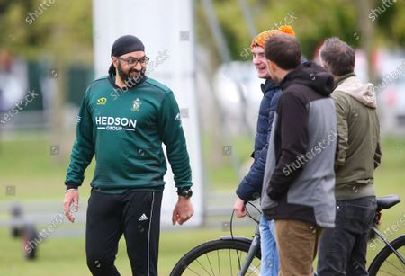 Ex-England International cricketer Monty Panesar playing for Twickenham Cricket Club while he studies for an MA in Sports Journalism at St Mary's University College, Twickenham. Here fielding on the boundary and chatting with spectators