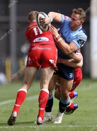 Hallam Amos of Cardiff Blues is tackled by Johnny McNicholl and Jonathan Davies of Scarlets.