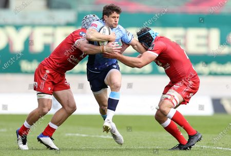 Lloyd Williams Cardiff Blues is tackled by Jonathan Davies and Iestyn Rees of Scarlets.