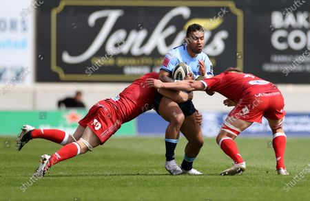 Willis Halaholo Cardiff Blues is tackled by Jonathan Davies and Josh Helps of Scarlets.