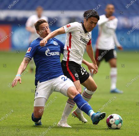 Bastian Oczipka of FC Schalke 04 (L) and Makoto Hasebe of Eintracht Frankfurt  battle for the ball during the Bundesliga match between FC Schalke 04 and Eintracht Frankfurt at Veltins-Arena on May 15, 2021 in Gelsenkirchen, Germany, 15 May 2021.