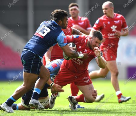 Rob Evans of Scarlets is tackled by Willis Halaholo of Cardiff Blues.