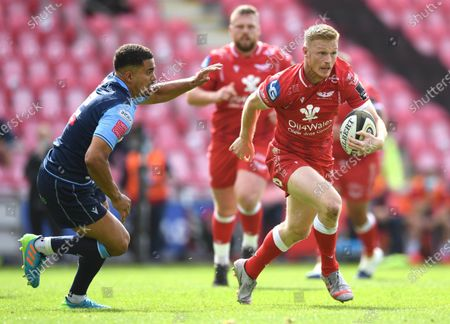 Johnny McNicholl of Scarlets gets past Ben Thomas of Cardiff Blues.