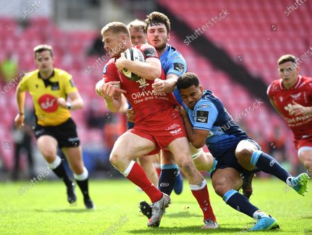 Johnny McNicholl of Scarlets is tackled by James Ratti and Ben Thomas of Cardiff Blues.