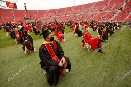 Roland Azerin graduating with a Masters from the Keck School of Medicine is socially distanced with all the students as USC student graduates from the 2020 and 2021 school year participated in the first of 14 USC's 2021 Commencement ceremonies at the Los Angeles Memorial Coliseum Friday May 14, 2021. There will be 2 ceremony's a day over the next 7 days. Students were spaced 8 feet apart on the field and spectators were social distanced in the stands at the Memorial Coliseum which has not held a USC commencement since 1950. Memorial Coliseum on Friday, May 14, 2021 in Los Angeles, CA. (Al Seib / Los Angeles Times).