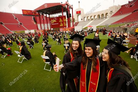 Emily Hernandez, Gisela Gonzalez and Johanna De Silva, left to right, all graduating with Masters in Physicians Assistant take a selfie as USC student graduates from the 2020 and 2021 school year participated in the first of 14 USC's 2021 Commencement ceremonies at the Los Angeles Memorial Coliseum Friday May 14, 2021. There will be 2 ceremony's a day over the next 7 days. Students were spaced 8 feet apart on the field and spectators were social distanced in the stands at the Memorial Coliseum which has not held a USC commencement since 1950. Memorial Coliseum on Friday, May 14, 2021 in Los Angeles, CA. (Al Seib / Los Angeles Times).