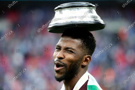 Leicester's Kelechi Iheanacho celebrates with the trophy plinth on his head after winning the FA Cup final soccer match between Chelsea and Leicester City at Wembley Stadium in London, England, . Leicester won 1-0
