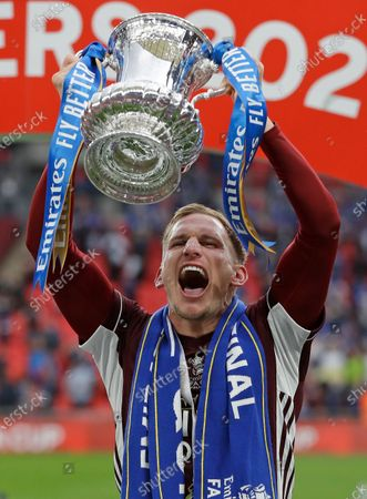 Leicester's Marc Albrighton holds the trophy aloft at the end of the FA Cup final soccer match between Chelsea and Leicester City at Wembley Stadium in London, England, . Leicester won the match 1-0