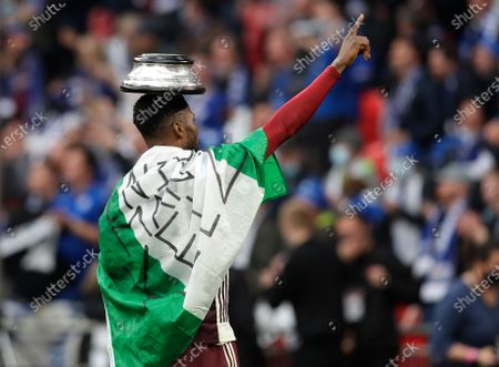 Leicester's Kelechi Iheanacho celebrate with the trophy stand on his head at the end of the FA Cup final soccer match between Chelsea and Leicester City at Wembley Stadium in London, England, . Leicester won the match 1-0