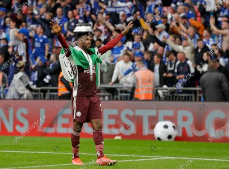 Leicester's Kelechi Iheanacho celebrates with the trophy stand on his head at the end of the FA Cup final soccer match between Chelsea and Leicester City at Wembley Stadium in London, England, . Leicester won the match 1-0