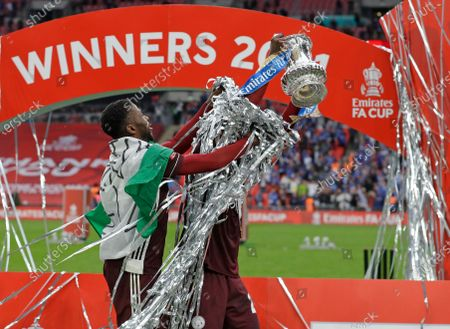 Leicester's Kelechi Iheanacho, left, and Leicester's Wilfred Ndidi celebrate with the trophy at the end of the FA Cup final soccer match between Chelsea and Leicester City at Wembley Stadium in London, England, . Leicester won the match 1-0