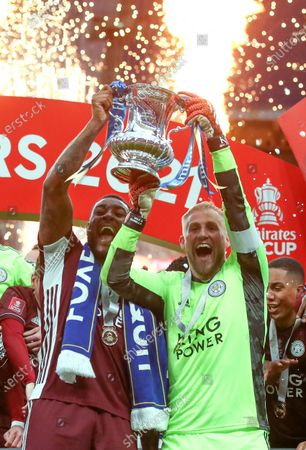 Leicester's goalkeeper Kasper Schmeichel (R) and Wes Morgan (L) celebrate with the trophy after winning the English FA Cup final between Chelsea FC and Leicester City at the Wembley Stadium in London, Britain, 15 May 2021.