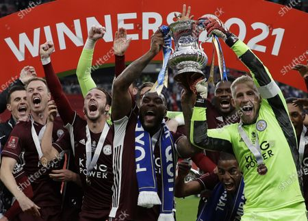 Leicester's Wes Morgan (C) and goalkeeper Kasper Schmeichel (R) celebrate with the trophy after winning the English FA Cup final between Chelsea FC and Leicester City at the Wembley Stadium in London, Britain, 15 May 2021.