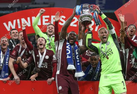 Leicester's goalkeeper Kasper Schmeichel (R) and Wes Morgan (C) celebrate with the trophy after winning the English FA Cup final between Chelsea FC and Leicester City at the Wembley Stadium in London, Britain, 15 May 2021.