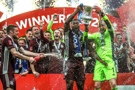 Leicester players Jamie Vardy (L), Wes Morgan (C), and goalkeeper Kasper Schmeichel (R) celebrate with the trophy after winning the English FA Cup final between Chelsea FC and Leicester City at the Wembley Stadium in London, Britain, 15 May 2021.
