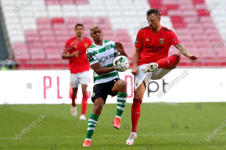 Stock Image of Haris Seferovic of SL Benfica (R ) vies with Joao Mario of Sporting CP during the Portuguese League football match between SL Benfica and Sporting CP at the Luz stadium in Lisbon, Portugal on May 15, 2021.