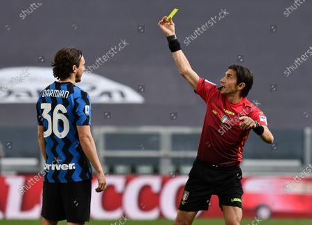 Referee Gianpaolo Calvarese shows the yellow card to Matteo Darmian of FC Internazionale