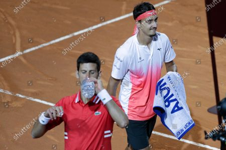 Stock Image of Serbia's Novak Djokovic drinks as Italy's Lorenzo Sonego walks past him, during their semi-final match at the Italian Open tennis tournament, in Rome