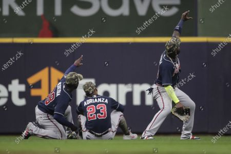 Atlanta Braves' Marcell Ozuna, right, poses with Ehire Adrianza (23) and Guillermo Heredia (38) after the the team's baseball game against the Milwaukee Brewers, in Milwaukee