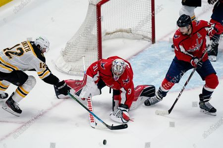 Boston Bruins right wing Craig Smith (12) and Washington Capitals goaltender Craig Anderson (31) and defenseman John Carlson (74) scramble for the puck during the second period of Game 1 of an NHL hockey Stanley Cup first-round playoff series, in Washington