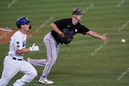 Miami Marlins relief pitcher Braxton Garrett, right, throws to first to out Los Angeles Dodgers' Will Smith, left, during the seventh inning of a baseball game, in Los Angeles