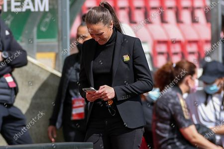 Manchester United Women Head Coach Casey Stoney checks her phone during the Women's FA Cup match between Manchester United Women and Leicester City at Leigh Sports Village, Leigh