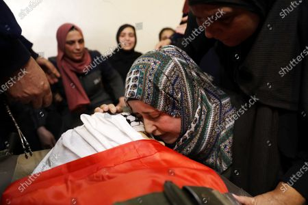 Family members mourn the death of Muhammad Yunus Freijat (15), who was killed during clashes with the Israeli army during a protest in the West Bank city of Hebron in the early morning, during his funeral in Hebron, 16 May 2021. In response to days of violent confrontations between Israeli security forces and Palestinians in Jerusalem, various Palestinian militants factions in Gaza launched rocket attacks since 10 May that killed at least ten Israelis to date. According to the Palestinian Ministry of Health, at least 174 people including 47 children and 29 women have been killed in Gaza in the recent retaliatory Israeli airstrikes.