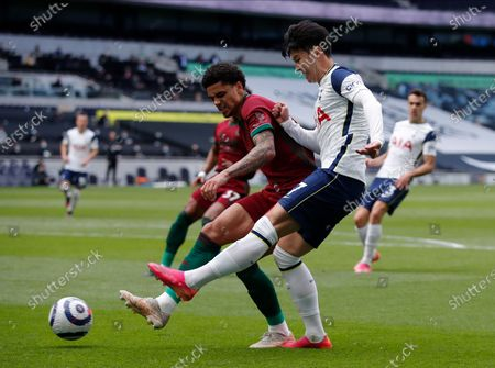 Tottenham's Son Heung-min, right, and Wolverhampton Wanderers' Ki-Jana Hoever challenge for the ball during the English Premier League soccer match between Tottenham Hotspur and Wolverhampton Wanderers at Tottenham Hotspur Stadium in London, England