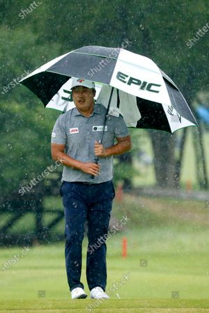 Kyoung-Hoon Lee, of South Korea, stands in a pouring rain studying the ninth green before his putt during the final round of the AT&T Byron Nelson golf tournament in McKinney, Texas