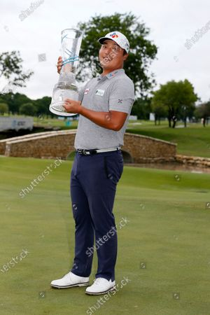 Kyoung-Hoon Lee, of South Korea, holds the trophy on the 18th green after winning the AT&T Byron Nelson golf tournament in McKinney, Texas