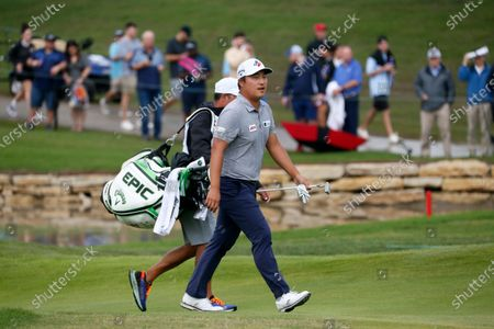 Lee, front, of South Korea, and his caddie, rear, walk onto the 18th green followed by the gallery during the final round of the AT&T Byron Nelson golf tournament in McKinney, Texas, . Lee won the tournament