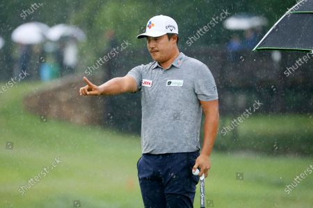 Kyoung-Hoon Lee of South Korea stands in a pouring rain as he lines up his putt on the ninth green during the final round of the AT&T Byron Nelson golf tournament in McKinney, Texas