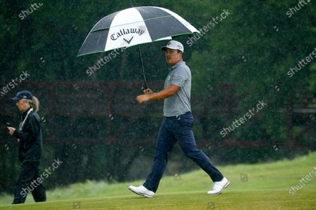 Kyoung-Hoon Lee, of South Korea, shields himself from a pouring rain as he works on the ninth green during the final round of the AT&T Byron Nelson golf tournament in McKinney, Texas